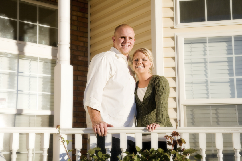 a couple standing on a home's front porch