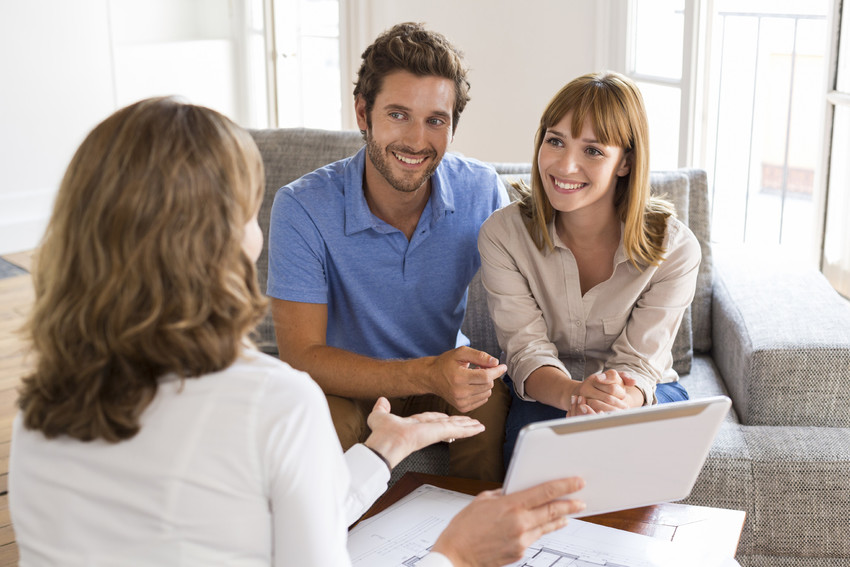 Woman smiling and explaining real estate to a couple sitting on a couch.