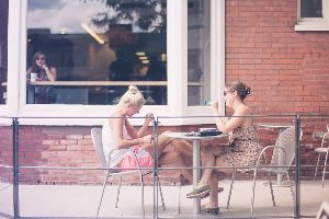 Two women sitting across from each other at an outdoor restaurant table.